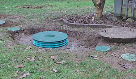 A ground shot of four green lids that are part of an on-site septic system.
