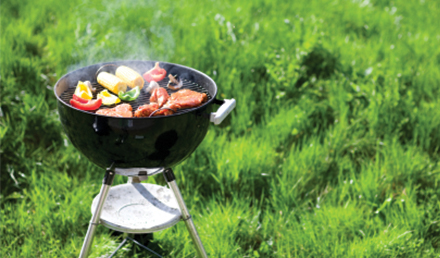 Black grill with meats and vegetables cooking in a yard