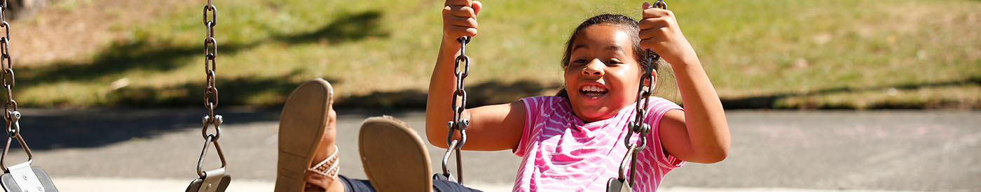 Smiling girl on swing.