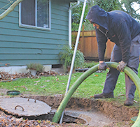 A septic professional pumping out a residential septic tank.