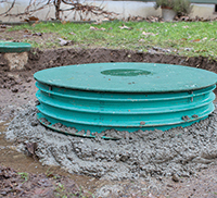Close up of a green septic system riser lid in a backyard