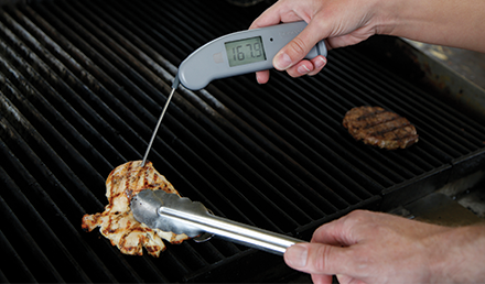 A digital food thermometer with a reading of 167 degrees from a grilled chicken breast held with cooking tongs