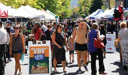 Crowd of people walking through a farmers market on a sunny day.