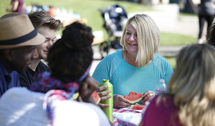 People seated at a park picnic table talking, smiling, eating fruit, and drinking water