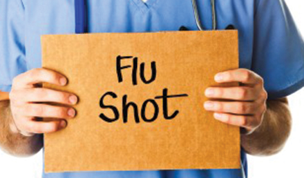 Healthcare worker holding a sign with the words flu shot.