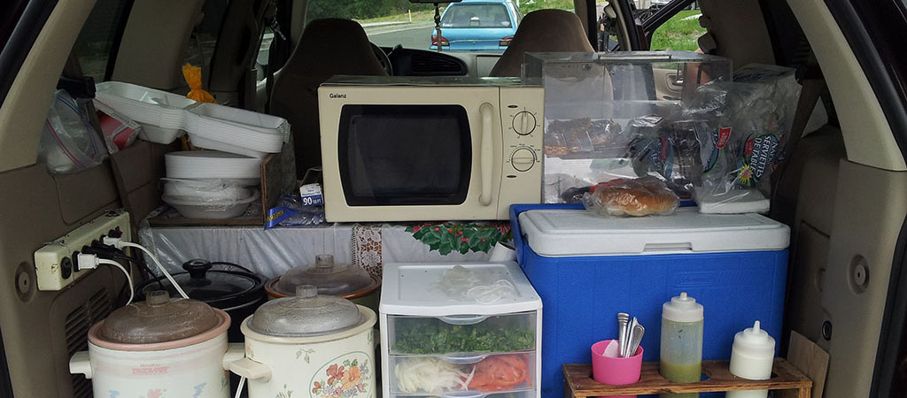 The back of an older van is filled with crockpots, food, condiments, a microwave, and a cooler.