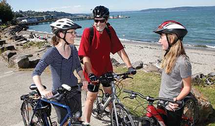 A woman, a man, and a young woman wearing bike helmets and each with bicycles standing near a beach talking.