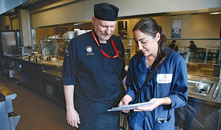 Food inspector showing a chef a food inspection report at a restaurant