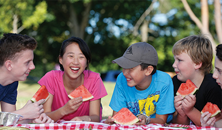 Five children lying on a picnic blanket while eating watermelon in a park