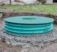 A green septic system riser lid above ground.