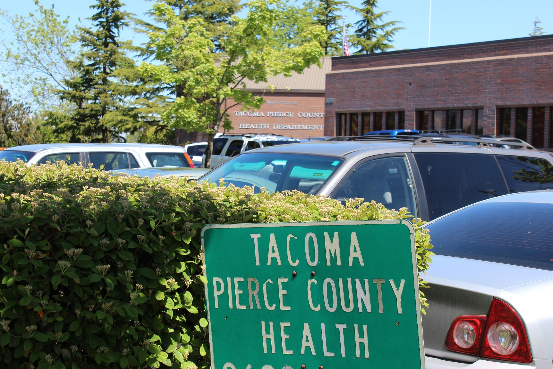 A sign reading Tacoma-Pierce County Health Department sits in front of a row of cars in the parking lot outside the building
