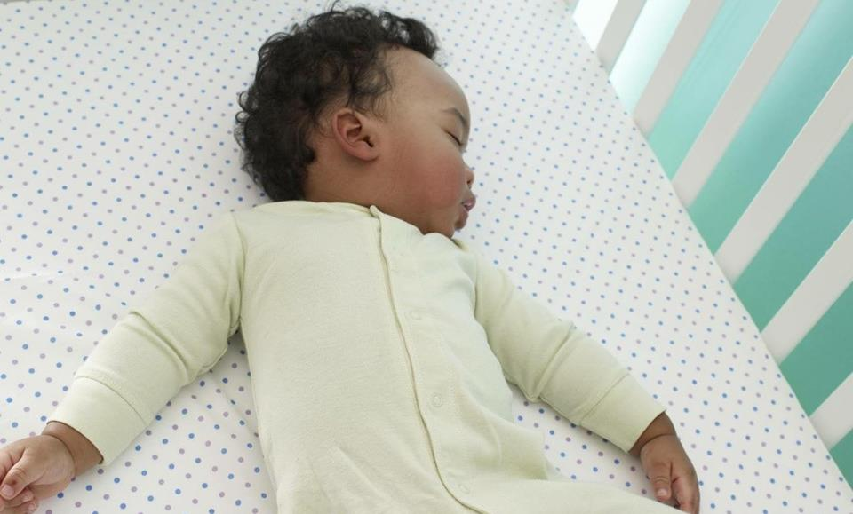 An infant sleeps safely, laying alone on its back in a crib.