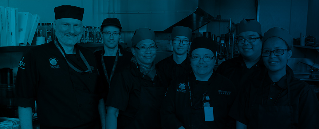 Five food workers in a commercial kitchen smiling while they look at the camera