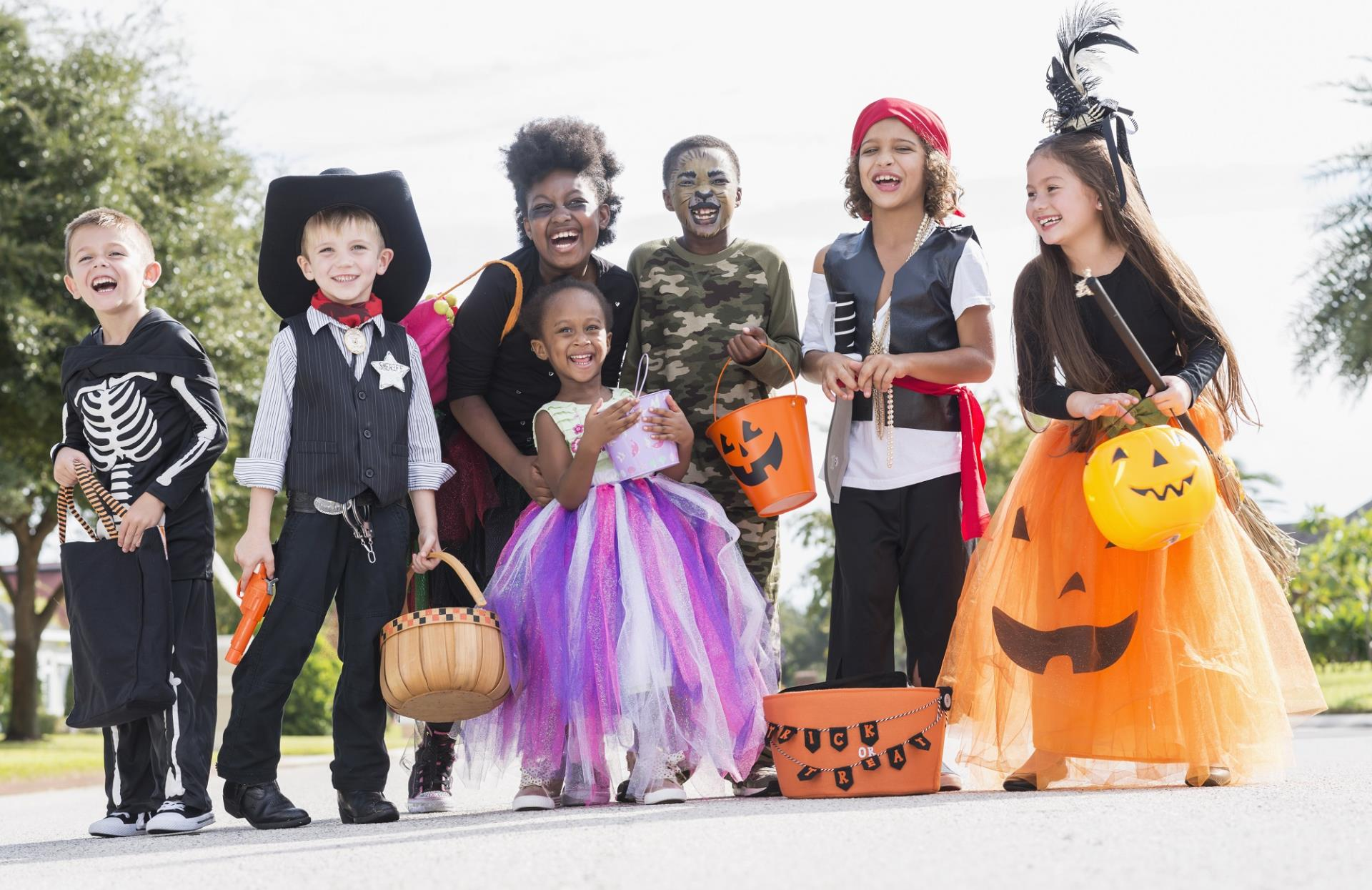 A group of children wearing Halloween costumes and carrying trick-or-treat baskets.