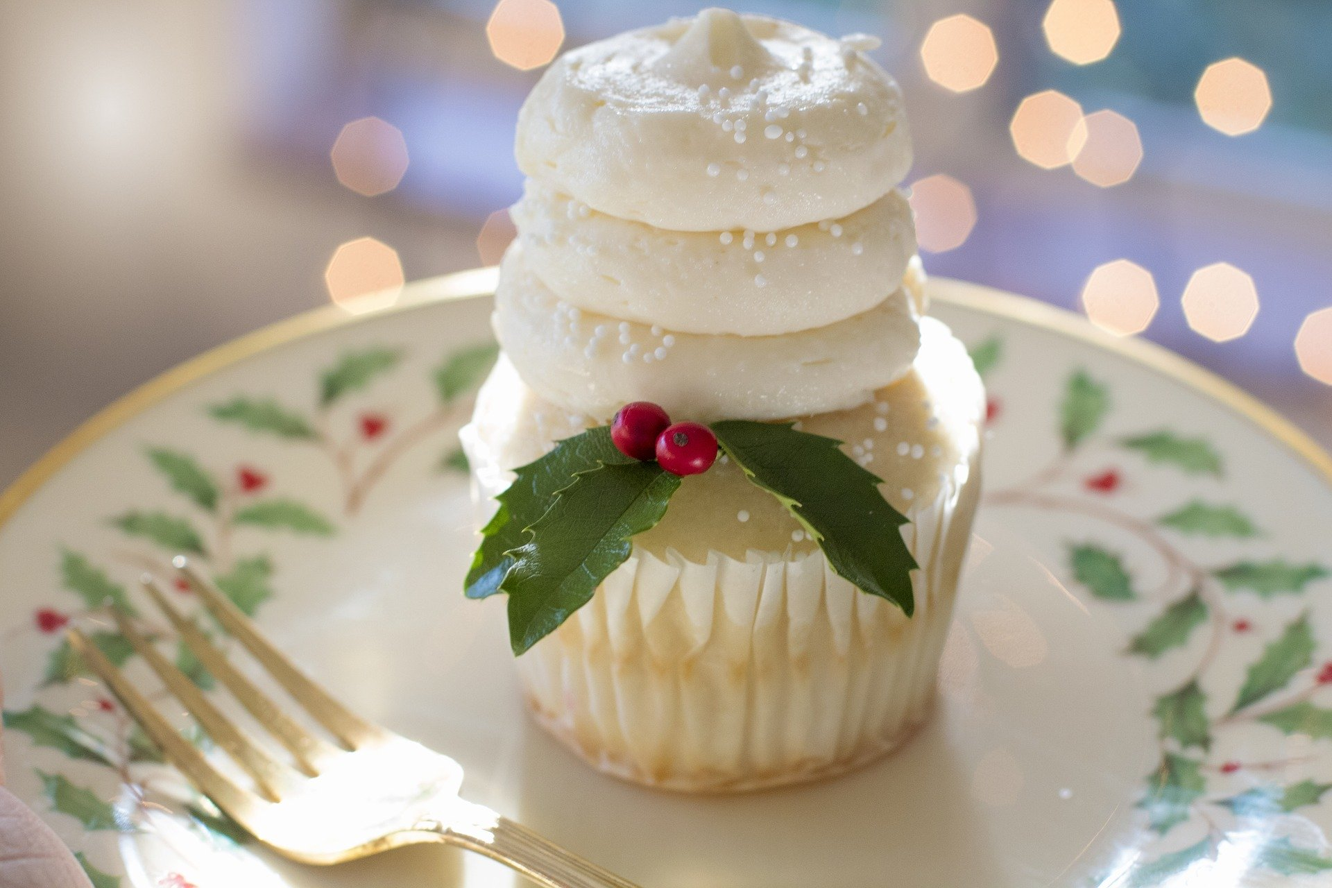 A cupcake sitting on a plate. Both are decorated for Christmas.