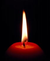 A burning candle against a dark background
