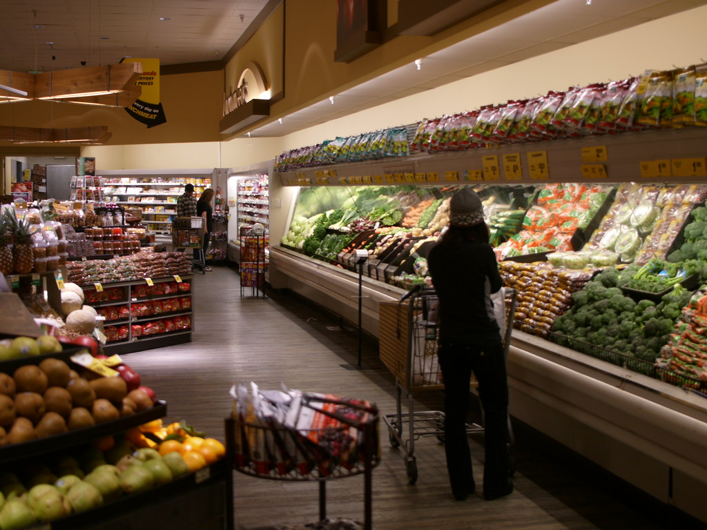 A woman looks at produce more than 6 feet away from other shoppers.