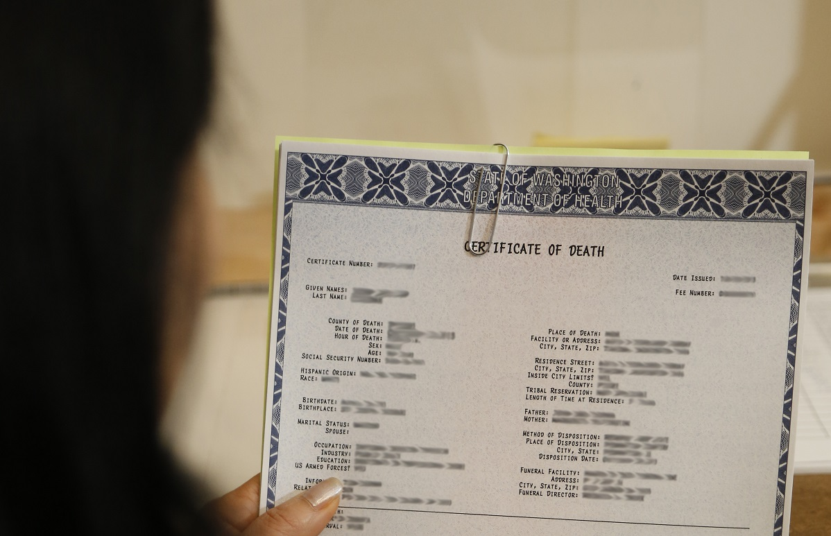 A woman holding a death certificate